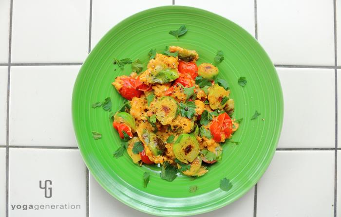 緑の器に入った芽キャベツとトマト入りメキシカンなスクランブルエッグ