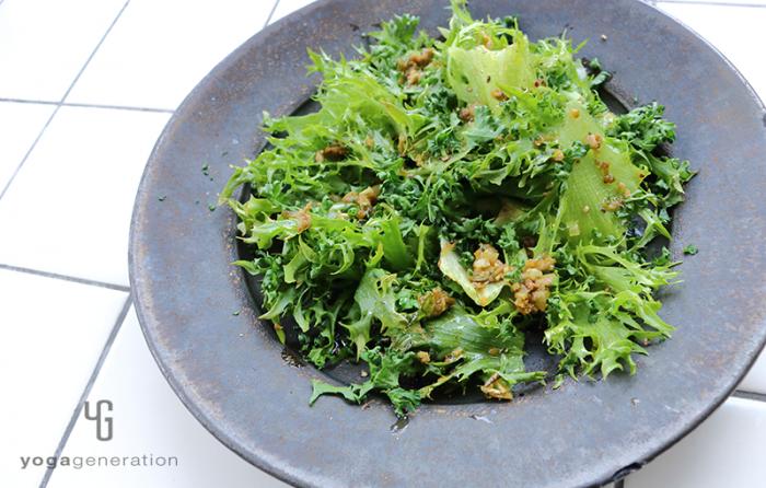 黒い皿に盛り付けたグリーンオリーブとアンチョビのガーリックオイル・サラダ