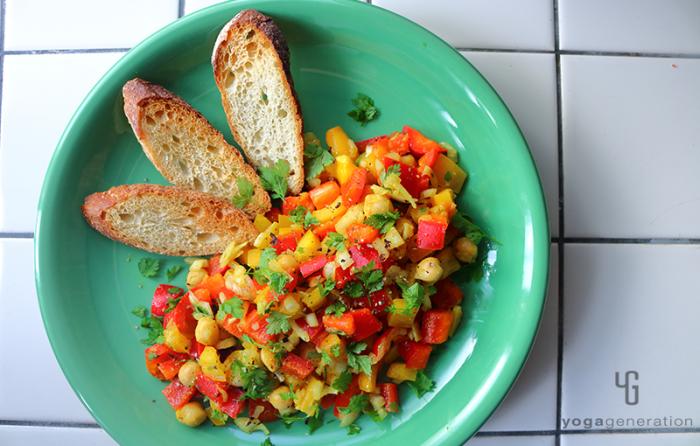緑の皿に盛り付けたヒヨコ豆とパプリカのスパイシー・カラフルサラダ