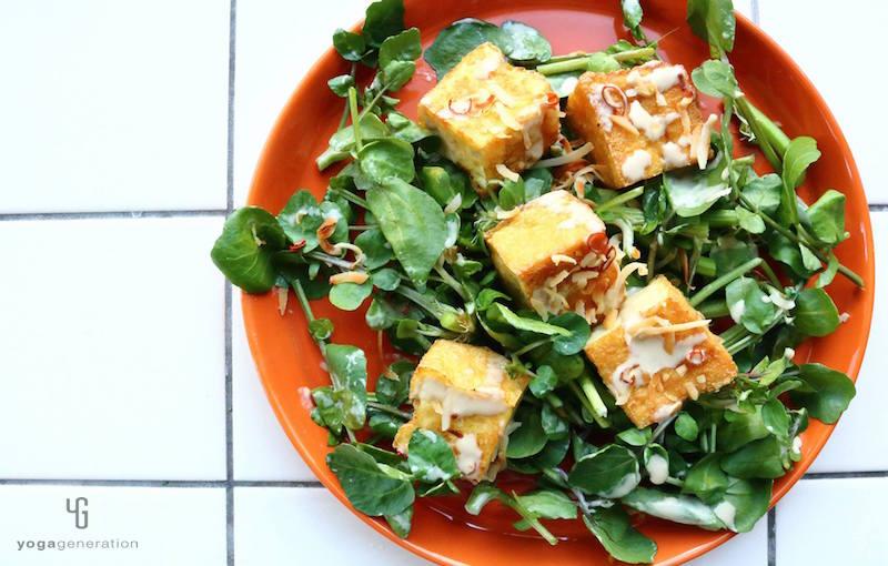 オレンジの皿に乗ったクレソンと厚揚げのサラダ