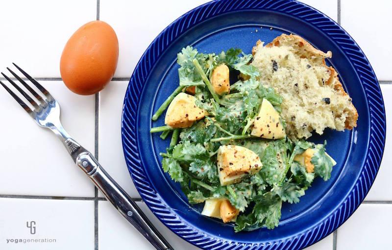 藍色の皿のサラダに乗ったパクチーとゆで卵パン添え