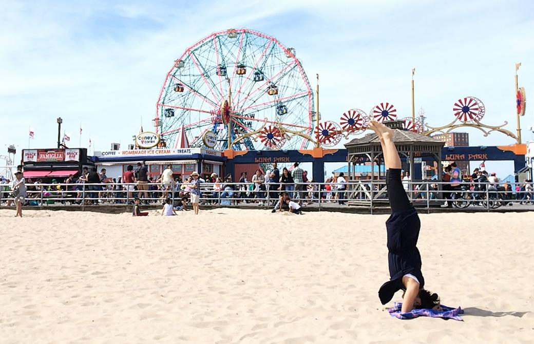 Mahokoがニューヨークのビーチでヘッドスタンドしている