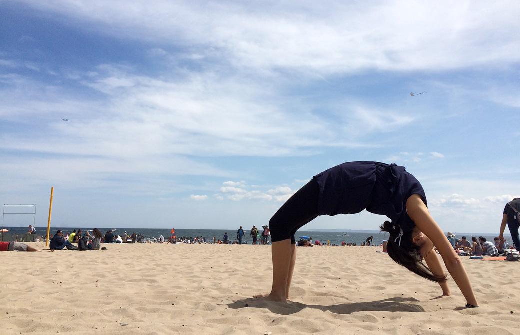 MahokoがNYのビーチで車輪のポーズをとっている