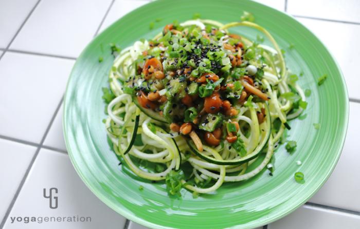 緑の皿に盛り付けたナメコ納豆ソースでズッキーニ・ヌードル