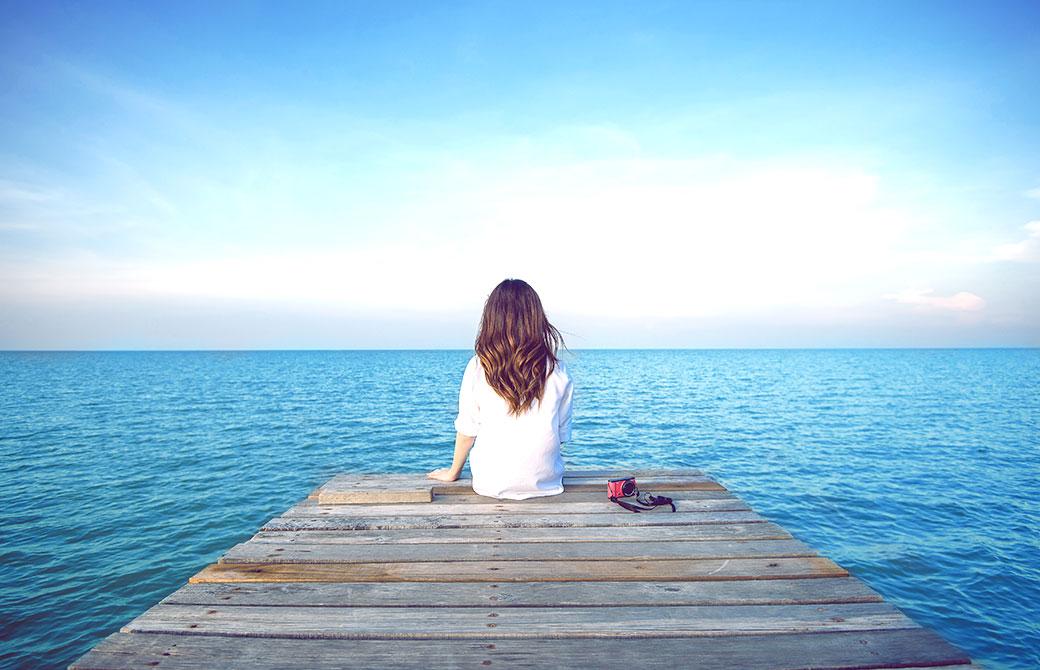 青空と海が広がる中、女性が1人で後ろ向きに座っている写真