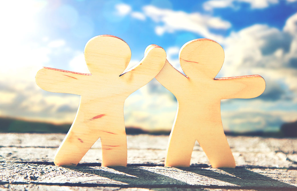 青空の下2人で仲良く手を繋いでいる画像