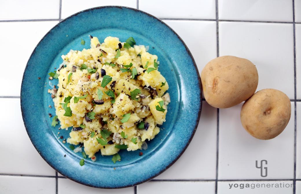 ターコイズの皿に盛りつけたラッキョウと黒オリーブのポテトサラダ