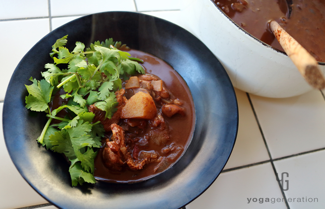 黒い器に盛りつけたジャガイモと鶏肉でメキシカン・スパイシー・チョコ・スープ