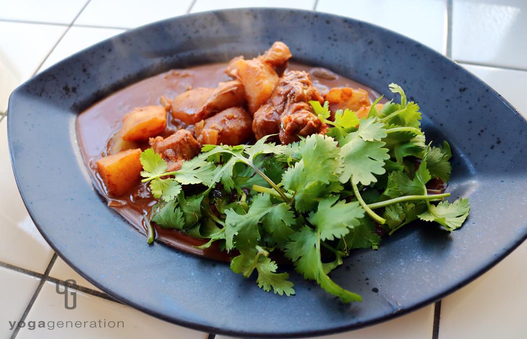 黒い楕円の器に盛りつけたジャガイモと鶏肉でメキシカン・スパイシー・チョコ・スープ