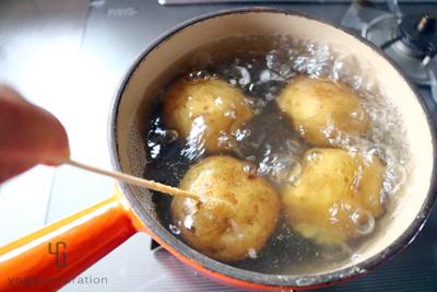 ジャガイモに竹串を通して茹で加減を確認する