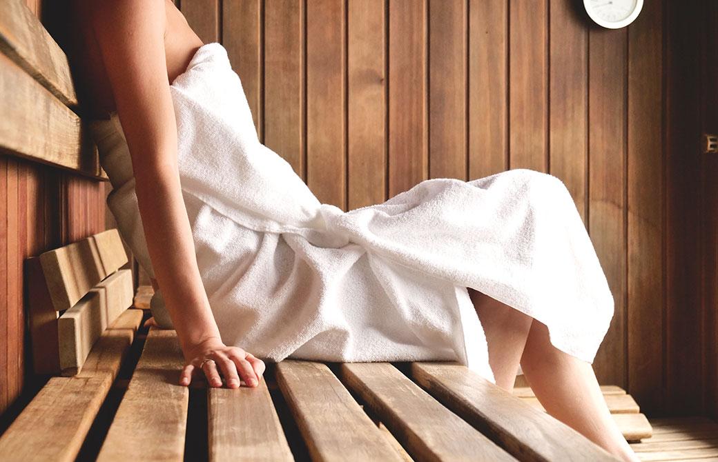 バスタオルを巻いた女性がサウナに入っている画像