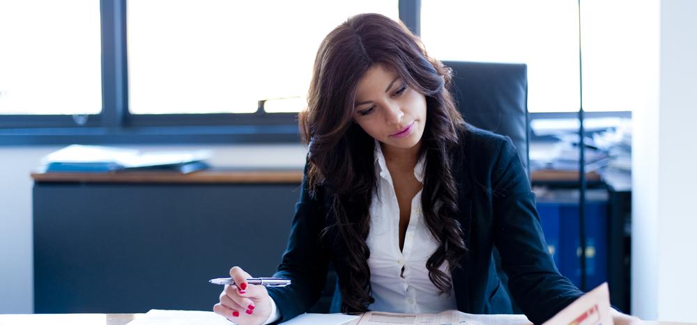 ペンを手に持ち書類を見る女性