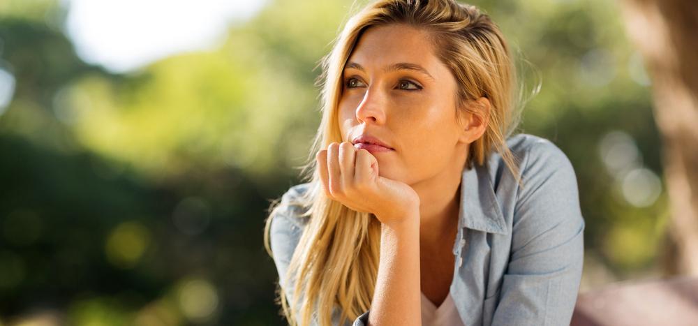 手に顎を乗せ遠くを見る女性