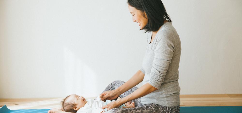 ヨガマットの上で赤ちゃんと見つめあうサントーシマ香先生