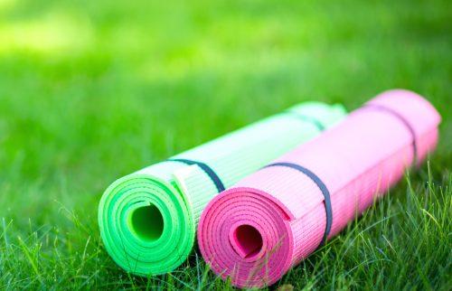 緑の芝生の上にピンクと緑のヨガマットが置かれた様子