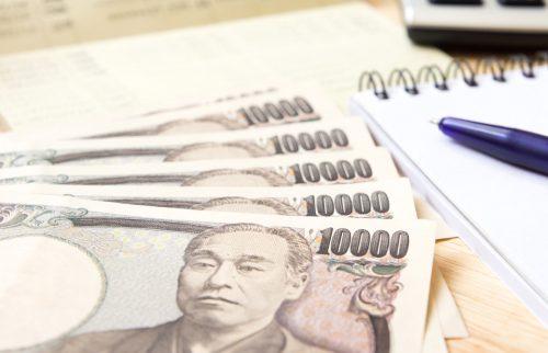 1万円札とMEMO帳が机の上に置かれている写真
