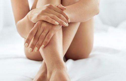 女性が三角座りをして足と腕を組んで座っている写真