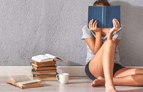 女性が本を読んでいる隣に本が積んである写真