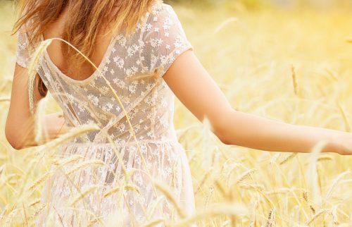 白い服を着た女性が草原の中を歩く様子