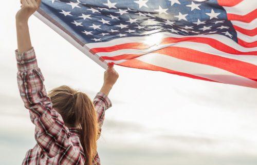 女性がアメリカの国旗を掲げて走る様子
