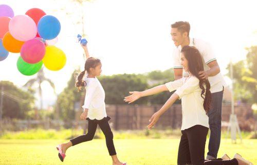 風船を持って走ってくる子供を母親と父親が待っている様子