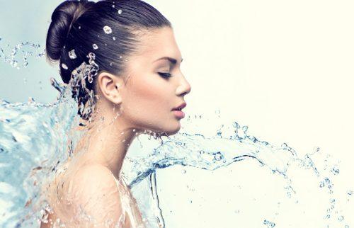 女性の顔に水がかかっているところを横から撮った写真
