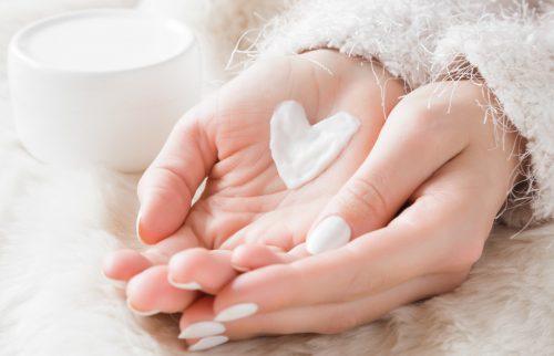 女性の手のひらに白いハート型の花びらがのった様子