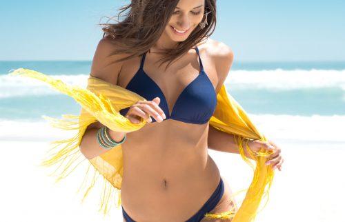 グレーの水着の女性が黄色のストールを身に着けて、ビーチを歩いている様子