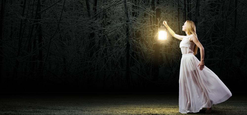 暗がりでランプを持つ女性