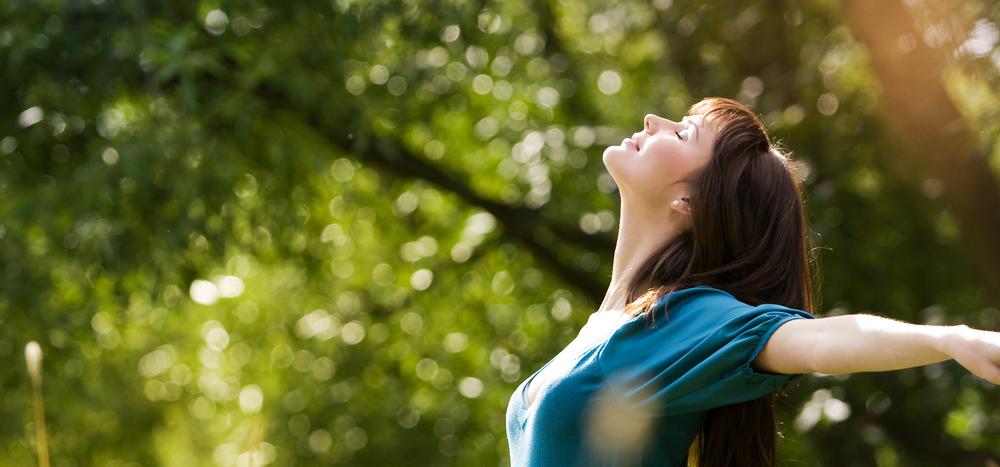 森の中で大きく息を吸う女性
