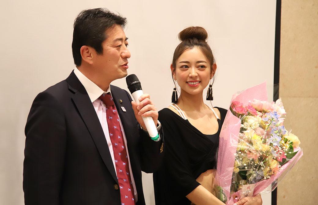 府中市長の高野律雄さんと花束を抱えた松本莉緒さん
