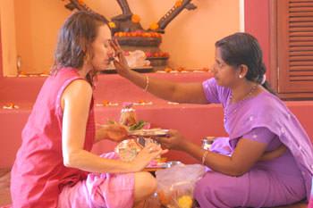 紫の服の女性が赤い服の女性の額に触れている