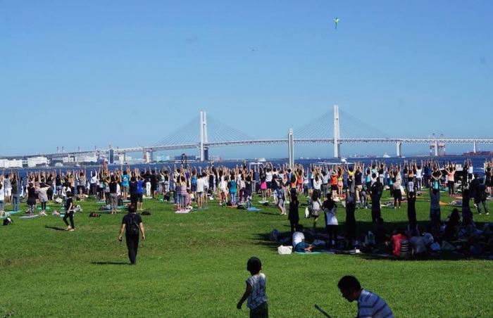 ベイブリッジが見える芝生の上でヨガをしている大勢の人々