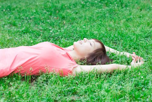 芝生で寝転がる女性