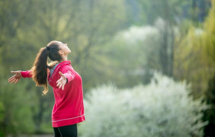 自然の中で大きく深呼吸する女性