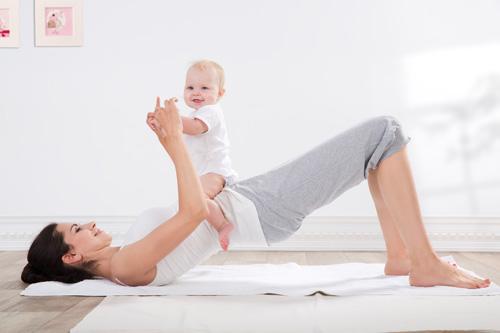 セツバンダアーサナする女性に赤ちゃんが乗っている