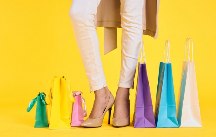 たくさんのカラフルな紙袋と女性の足