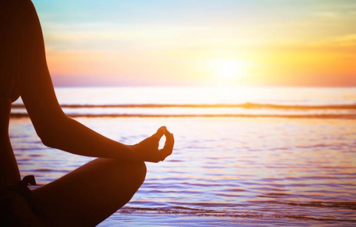 ビーチに座り瞑想する人の影