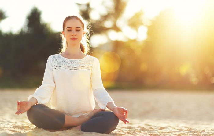 女性が砂浜に座り瞑想している