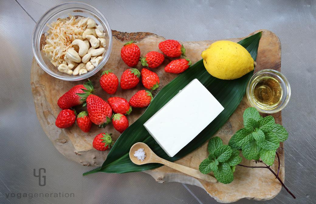 木製カットボードの上のイチゴやレモン、ナッツなどの材料