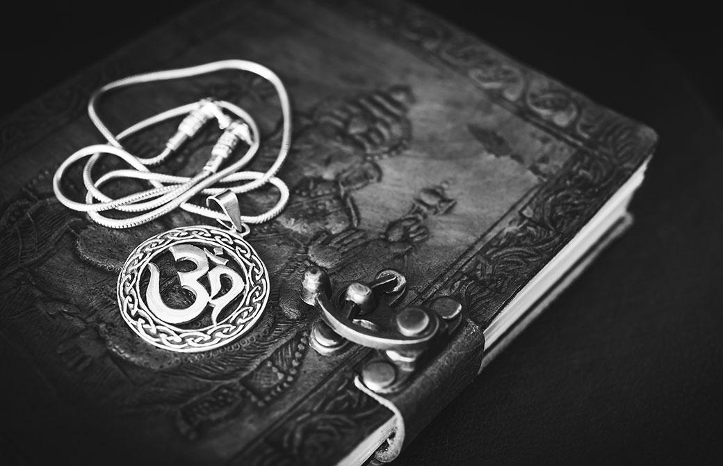 オームのマークのペンダントと古い本