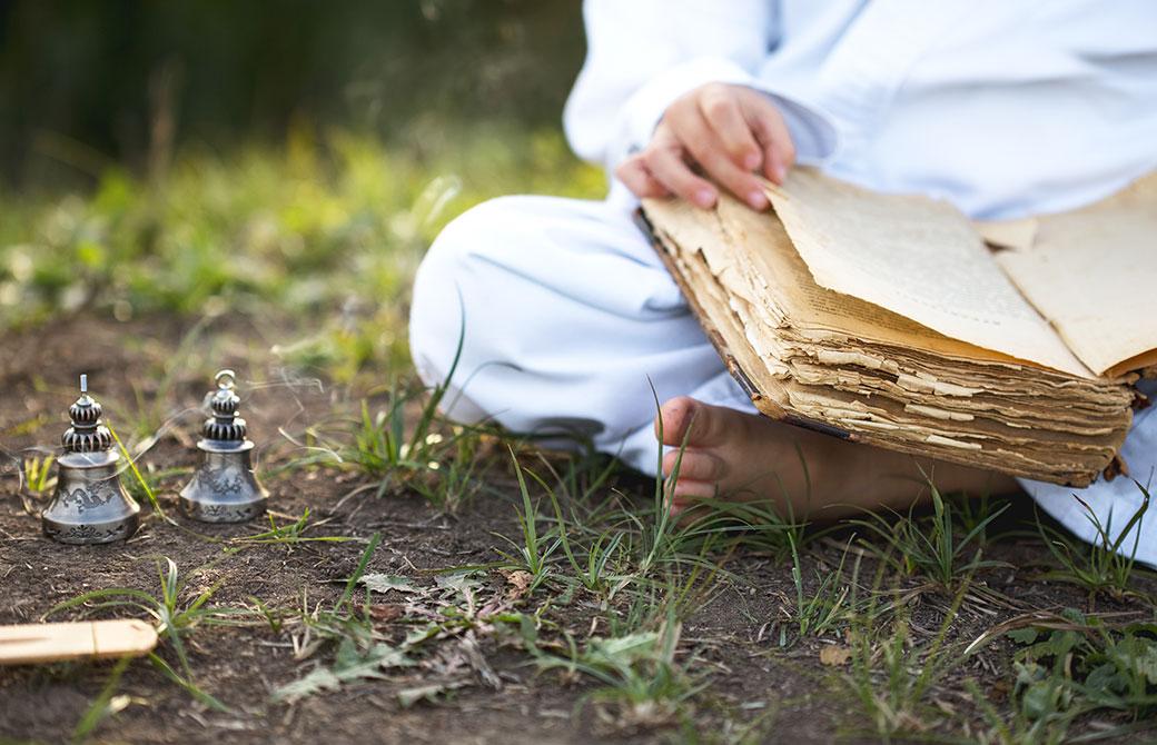 地面の上で白い服を着た男性が古書を読んでいる様子