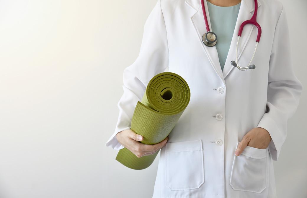 白衣を着た医師がヨガマットを持っている