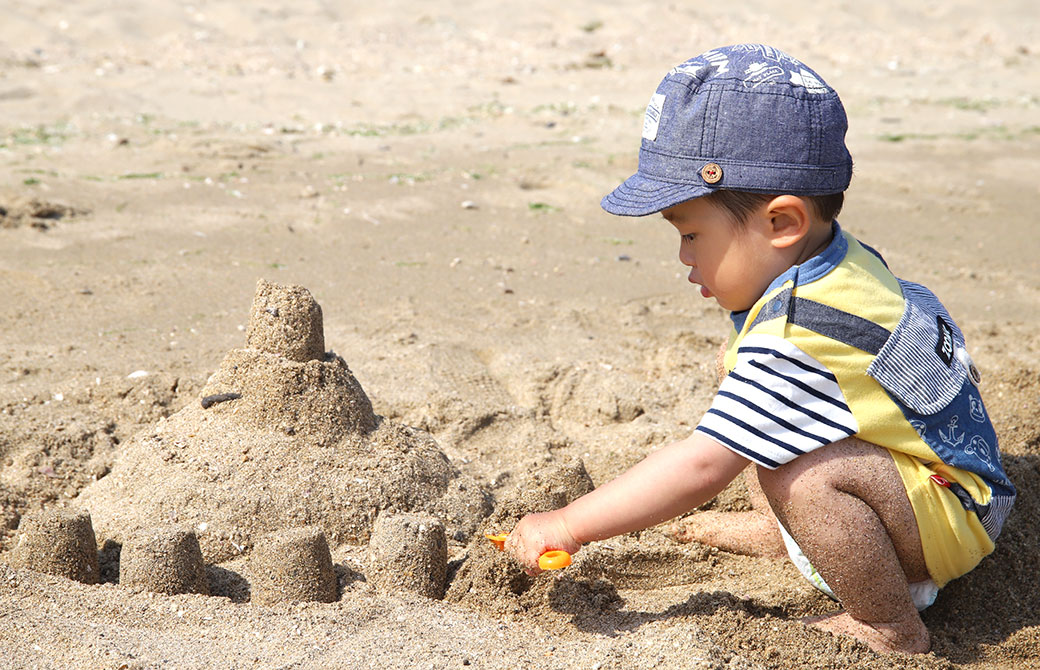 kaya息子が海でお城を作って遊んでいる写真