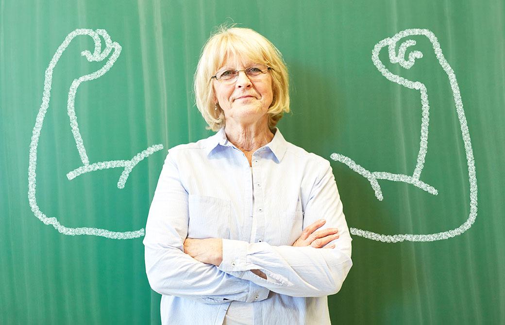 女性が腕の筋肉が描かれた黒板の前に経っている写真