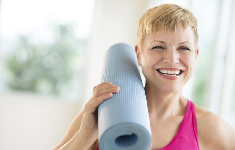 笑顔で丸めたヨガマットを肩に乗せる女性