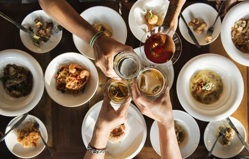 様々な料理の上で4人の手が乾杯している