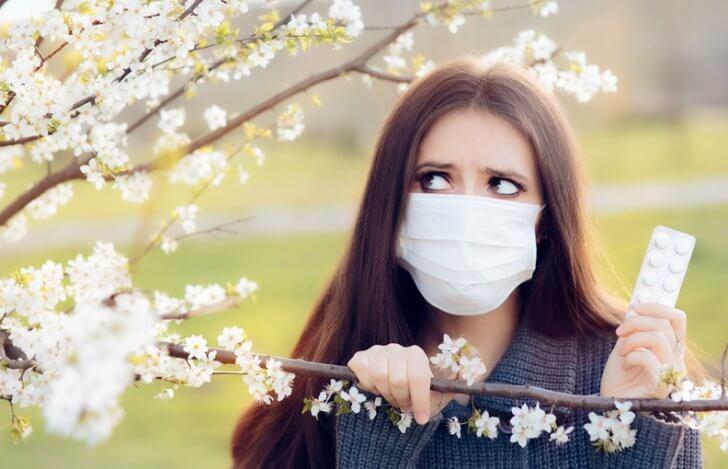マスクをした女性が錠剤を持って桜の木の下にいる