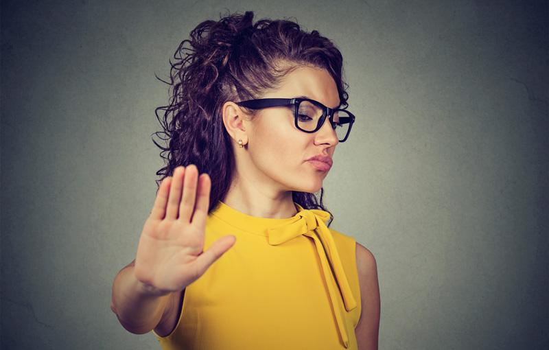 手のひらを前に向け顔をそむける女性