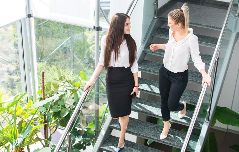 同僚と笑顔で談笑しながら階段を降りる女性たち